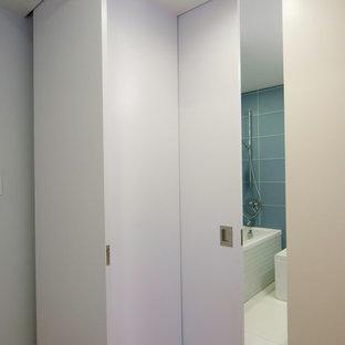 Modelo de cuarto de baño principal, actual, pequeño, con armarios abiertos, puertas de armario de madera clara, bañera empotrada, sanitario de una pieza, baldosas y/o azulejos azules, baldosas y/o azulejos de vidrio, paredes rosas, suelo de cemento, lavabo integrado y encimera de cemento