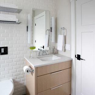 Foto de cuarto de baño con ducha, de estilo americano, de tamaño medio, con puertas de armario blancas, bañera empotrada, combinación de ducha y bañera, sanitario de pared, baldosas y/o azulejos blancos, baldosas y/o azulejos de cerámica, paredes blancas, suelo de baldosas de porcelana, lavabo bajoencimera, encimera de cuarzo compacto, suelo gris, ducha con puerta con bisagras, encimeras blancas y armarios con paneles lisos