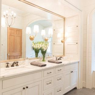 ニューオリンズの広いトラディショナルスタイルのおしゃれなマスターバスルーム (落し込みパネル扉のキャビネット、白いキャビネット、白い壁、磁器タイルの床、アンダーカウンター洗面器、グレーの床、グレーの洗面カウンター、洗面台2つ、造り付け洗面台、格子天井、塗装板張りの壁) の写真