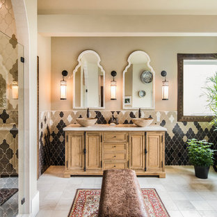 Design ideas for a mediterranean ensuite bathroom in Seattle with freestanding cabinets, light wood cabinets, a freestanding bath, ceramic tiles, beige walls, ceramic flooring, a vessel sink, marble worktops, a hinged door, an alcove shower, beige tiles, brown tiles, grey tiles, white tiles and beige floors.