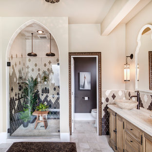 Example of a tuscan master ceramic tile, beige tile, gray tile and white tile ceramic floor and beige floor bathroom design in Seattle with furniture-like cabinets, light wood cabinets, beige walls, a vessel sink, marble countertops and a hinged shower door