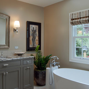 Mid-sized elegant ceramic tile and beige tile porcelain floor freestanding bathtub photo in Portland with beaded inset cabinets, brown cabinets, an undermount sink, granite countertops and beige walls