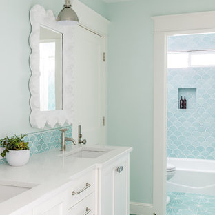 Idéer för att renovera ett mellanstort vintage badrum för barn, med vita skåp, ett badkar i en alkov, en dusch/badkar-kombination, grön kakel, blå kakel, keramikplattor, gröna väggar, cementgolv, ett undermonterad handfat, bänkskiva i kvarts, turkost golv, dusch med duschdraperi och luckor med infälld panel