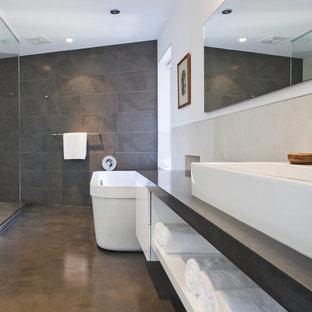 Ejemplo de cuarto de baño moderno con bañera exenta, lavabo sobreencimera, suelo de cemento, ducha abierta, ducha abierta y baldosas y/o azulejos de pizarra
