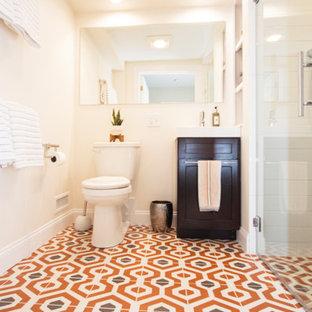 Kleines Stilmix Badezimmer En Suite mit Schrankfronten mit vertiefter Füllung, dunklen Holzschränken, bodengleicher Dusche, Wandtoilette mit Spülkasten, weißen Fliesen, Metrofliesen, beiger Wandfarbe, Mosaik-Bodenfliesen, Einbauwaschbecken, orangem Boden und Falttür-Duschabtrennung in Providence