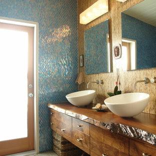 Foto di una grande stanza da bagno padronale tropicale con ante in legno bruno, top in legno, piastrelle blu, lavabo a bacinella, pavimento con piastrelle di ciottoli, ante lisce, piastrelle di vetro e pareti marroni