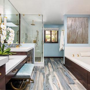 Modelo de cuarto de baño principal, tradicional renovado, de tamaño medio, con armarios tipo vitrina, puertas de armario de madera en tonos medios, bañera encastrada, ducha esquinera, baldosas y/o azulejos blancos, baldosas y/o azulejos de porcelana, paredes azules, suelo de madera en tonos medios, lavabo bajoencimera, encimera de cuarzo compacto, suelo multicolor, ducha con puerta con bisagras y encimeras blancas