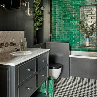 Photo of a traditional shower room in London with grey cabinets, a built-in bath, a shower/bath combination, green tiles, grey walls, a submerged sink, multi-coloured floors and an open shower.