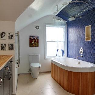 Modelo de cuarto de baño bohemio con bañera exenta, encimera de madera y encimeras marrones
