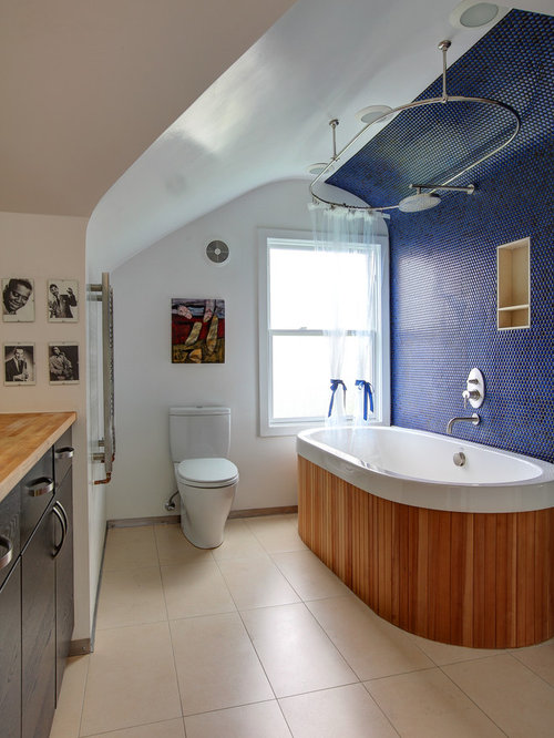 example of an eclectic bathtub design in portland with wood countertops