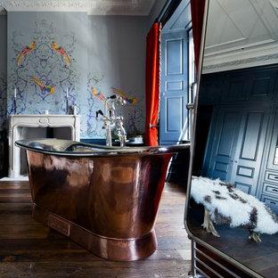 Foto de cuarto de baño bohemio con bañera exenta, paredes azules, suelo de madera oscura y suelo marrón