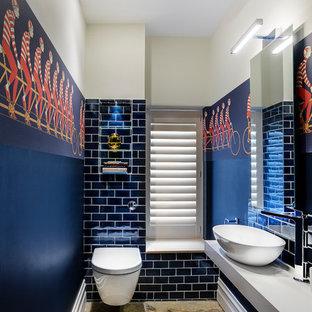 Immagine di una piccola stanza da bagno per bambini bohémian con WC sospeso, piastrelle nere, piastrelle diamantate, pavimento in pietra calcarea, lavabo a bacinella, top in superficie solida e pareti grigie