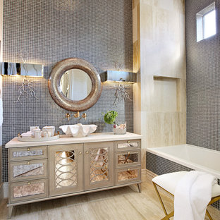 Example of an eclectic gray tile and mosaic tile alcove bathtub design in Las Vegas with a vessel sink, furniture-like cabinets and beige cabinets