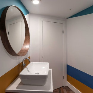 Small eclectic 3/4 brick floor and brown floor corner shower photo in Vancouver with flat-panel cabinets, medium tone wood cabinets, a one-piece toilet, multicolored walls, a vessel sink, solid surface countertops and white countertops