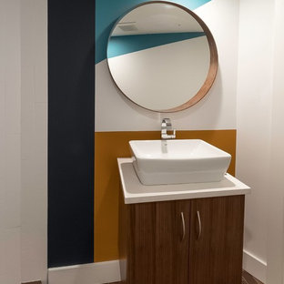 Corner shower - small eclectic 3/4 brick floor and brown floor corner shower idea in Vancouver with flat-panel cabinets, medium tone wood cabinets, a one-piece toilet, multicolored walls, a vessel sink, solid surface countertops and white countertops
