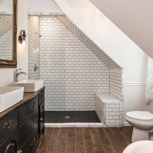 This is an example of a mid-sized eclectic master bathroom in Nashville with a vessel sink, black cabinets, wood benchtops, an alcove shower, a two-piece toilet, black and white tile, porcelain tile, white walls, porcelain floors, brown floor and brown benchtops.