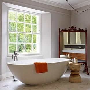 Modelo de cuarto de baño asiático, de tamaño medio, con bañera exenta, suelo de mármol, lavabo suspendido, ducha a ras de suelo, sanitario de pared, baldosas y/o azulejos multicolor, baldosas y/o azulejos de porcelana y paredes grises