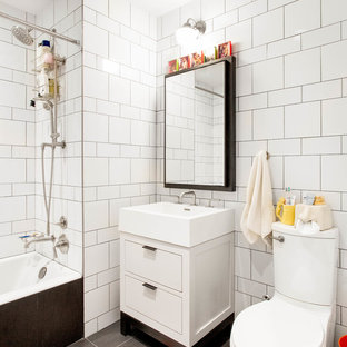 Inspiration for a mid-sized eclectic 3/4 white tile and subway tile gray floor and porcelain floor bathroom remodel in New York with flat-panel cabinets, white cabinets, a two-piece toilet and a console sink
