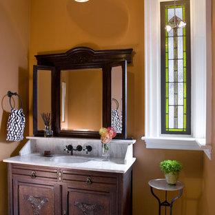 Foto di una stanza da bagno vittoriana con lavabo sottopiano, ante con riquadro incassato, ante in legno bruno e pareti arancioni