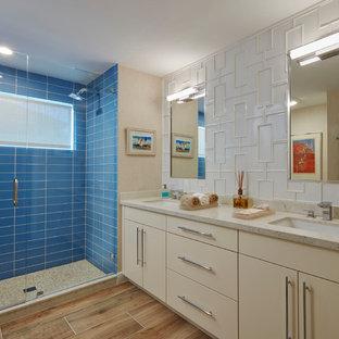 Foto di una stanza da bagno con doccia stile marinaro con ante lisce, ante beige, doccia alcova, piastrelle blu, piastrelle di vetro, lavabo sottopiano, porta doccia a battente e pavimento beige