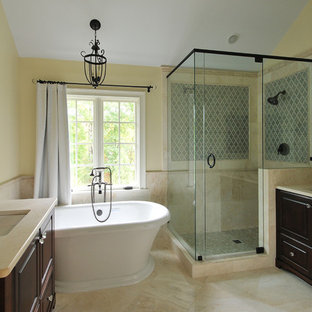 Inspiration for a traditional bathroom in Atlanta with a freestanding tub, yellow walls and travertine.