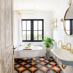 Design ideas for a mediterranean bathroom in Los Angeles with a claw-foot bath, white tiles, metro tiles, cement flooring, a wall-mounted sink, multi-coloured floors and double sinks.