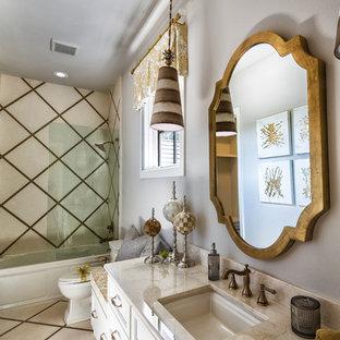 Ejemplo de cuarto de baño con ducha, bohemio, de tamaño medio, con armarios con paneles empotrados, puertas de armario blancas, baldosas y/o azulejos blancos, baldosas y/o azulejos beige, baldosas y/o azulejos de mármol, paredes blancas, suelo con mosaicos de baldosas, lavabo bajoencimera, encimera de mármol, bañera empotrada, combinación de ducha y bañera y sanitario de dos piezas
