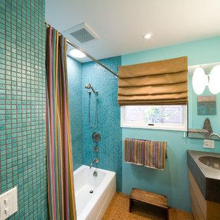 Modelo de cuarto de baño con ducha, contemporáneo, de tamaño medio, con encimera de cemento, ducha con cortina, armarios con paneles lisos, puertas de armario de madera oscura, bañera empotrada, combinación de ducha y bañera, baldosas y/o azulejos azules, baldosas y/o azulejos en mosaico, paredes azules, suelo de corcho, lavabo integrado, suelo marrón y encimeras grises