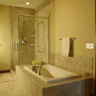 Modelo de cuarto de baño principal, tradicional, de tamaño medio, con armarios con paneles empotrados, puertas de armario de madera oscura, bañera encastrada, ducha esquinera, sanitario de una pieza, paredes amarillas, baldosas y/o azulejos de porcelana, suelo de travertino y encimera de azulejos