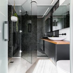 Bild på ett funkis brun brunt badrum med dusch, med släta luckor, svarta skåp, en kantlös dusch, svart kakel, vita väggar, ett fristående handfat, träbänkskiva, grått golv och dusch med gångjärnsdörr