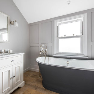 Ispirazione per una stanza da bagno classica con ante a filo, ante bianche, vasca freestanding, pareti grigie, parquet chiaro e lavabo sottopiano