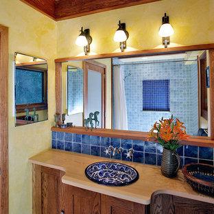 Esempio di una stanza da bagno mediterranea con lavabo da incasso, top in legno, pareti gialle e top beige