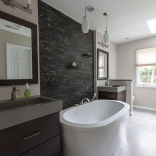 Свежая идея для дизайна: большая главная ванная комната в стиле лофт с монолитной раковиной, плоскими фасадами, темными деревянными фасадами, столешницей из бетона, отдельно стоящей ванной, душем в нише, раздельным унитазом, серой плиткой, керамогранитной плиткой, серыми стенами и полом из керамогранита - отличное фото интерьера
