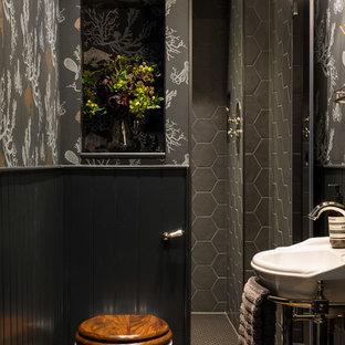 他の地域のトランジショナルスタイルのおしゃれなバスルーム (浴槽なし) (グレーのタイル、マルチカラーの壁、コンソール型シンク、壁掛け式トイレ) の写真