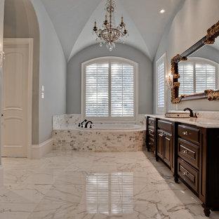 Ispirazione per una grande stanza da bagno padronale classica con ante con bugna sagomata, ante in legno bruno, vasca da incasso, piastrelle beige, piastrelle bianche, lastra di pietra, top in marmo, pareti grigie, pavimento in marmo, lavabo sottopiano e pavimento bianco