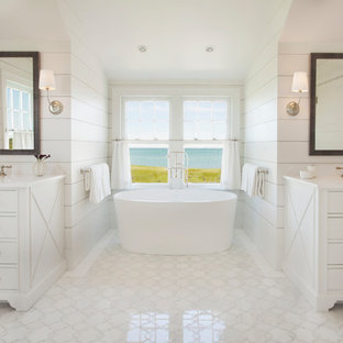 Example of a beach style master white floor freestanding bathtub design in Boston with white cabinets and white walls
