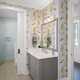Mid-sized elegant blue tile and glass tile ceramic tile, brown floor, single-sink and wallpaper bathroom photo in Grand Rapids with shaker cabinets, gray cabinets, multicolored walls, an undermount sink, quartz countertops, a hinged shower door, white countertops and a built-in vanity