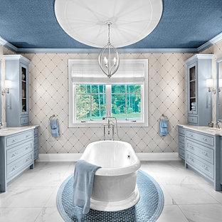 グランドラピッズの広いトラディショナルスタイルのおしゃれなマスターバスルーム (シェーカースタイル扉のキャビネット、青いキャビネット、置き型浴槽、オープン型シャワー、ベージュの壁、セラミックタイルの床、アンダーカウンター洗面器、クオーツストーンの洗面台、マルチカラーの床、白い洗面カウンター、トイレ室、洗面台1つ、造り付け洗面台、クロスの天井、壁紙) の写真