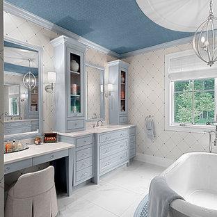 На фото: большая главная ванная комната в классическом стиле с фасадами в стиле шейкер, синими фасадами, отдельно стоящей ванной, открытым душем, бежевыми стенами, полом из керамической плитки, врезной раковиной, столешницей из искусственного кварца, разноцветным полом, белой столешницей, унитазом, тумбой под одну раковину, встроенной тумбой и потолком с обоями