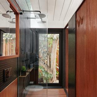 Imagen de cuarto de baño con ducha, asiático, con ducha doble, sanitario de una pieza, baldosas y/o azulejos negros, paredes marrones y ducha abierta