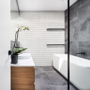 Photo of a contemporary master bathroom in Sydney with medium wood cabinets, a freestanding tub, a curbless shower, gray tile, a vessel sink, grey floor and white benchtops.