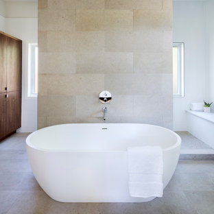 Design ideas for a mid-sized contemporary master bathroom in Austin with a freestanding tub, gray tile, white walls, limestone, an open shower, porcelain floors, beige floor and an open shower.
