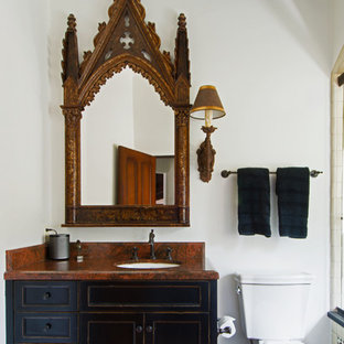Imagen de cuarto de baño mediterráneo con armarios estilo shaker, paredes blancas, puertas de armario con efecto envejecido y encimeras rojas