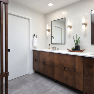 Inspiration for a mid-sized mid-century modern master gray tile and porcelain tile porcelain tile, gray floor, double-sink and wood wall bathroom remodel in Phoenix with flat-panel cabinets, medium tone wood cabinets, a one-piece toilet, white walls, an undermount sink, quartz countertops, white countertops, a niche and a built-in vanity