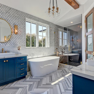 Inspiration for a beach style master multicolored floor bathroom remodel in Los Angeles with shaker cabinets, blue cabinets, multicolored walls, a vessel sink, a hinged shower door and gray countertops