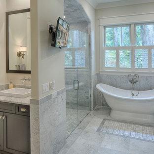 Immagine di una stanza da bagno padronale country di medie dimensioni con ante con riquadro incassato, ante in legno bruno, vasca freestanding, doccia a filo pavimento, piastrelle grigie, pareti beige, pavimento in marmo, lavabo da incasso e top in marmo