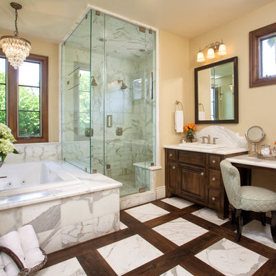 Inspiration for a tropical white tile and stone tile bathroom remodel in San Diego with raised-panel cabinets, dark wood cabinets and marble countertops