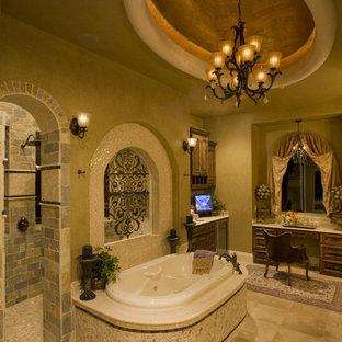 Foto di una grande stanza da bagno padronale mediterranea con ante con bugna sagomata, ante in legno bruno, vasca da incasso, doccia aperta, WC a due pezzi, pareti beige, pavimento con piastrelle in ceramica, lavabo sottopiano e top in granito