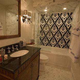 Diseño de cuarto de baño infantil, clásico, de tamaño medio, con armarios tipo mueble, puertas de armario de madera en tonos medios, bañera empotrada, combinación de ducha y bañera, sanitario de una pieza, baldosas y/o azulejos beige, baldosas y/o azulejos de mármol, paredes beige, suelo de mármol, lavabo bajoencimera, encimera de ónix, suelo blanco, ducha abierta y encimeras negras