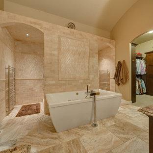Cette photo montre une salle de bain chic avec des portes de placard en bois sombre, une baignoire indépendante, un carrelage beige et du carrelage en travertin.